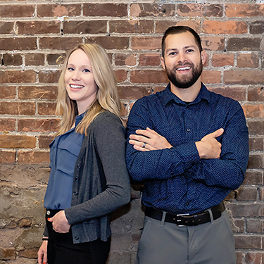 Dr. Brielle Egilson & Dr. Nick Lee standing in Enlighten Chiropractic in Lakeville MN