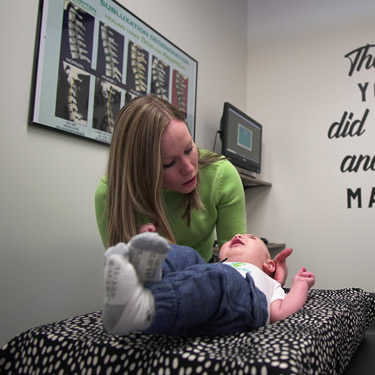 Dr. Brielle Egilson adjusting a baby in Enlighten Chiropractic in Lakeville MN