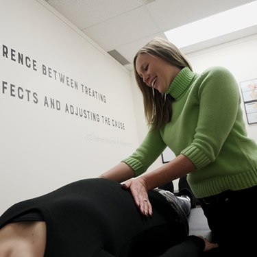 Dr. Brielle Egilson checking pregnant woman in Enlighten Chiropractic in Lakeville MN
