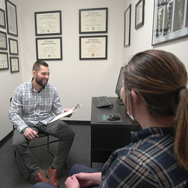 Dr. Nick Lee giving patient evaluation at Enlighten Chiropractic in Lakeville MN