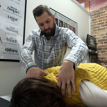 Dr. Nick Lee shoulder adjustment with patient in Enlighten Chiropractic in Lakeville MN